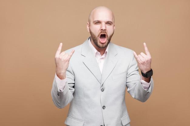 ロックンロール。ロックサインで立ってカメラを見ている古典的な灰色のスーツでハンサムな中年のハゲひげを生やしたビジネスマンを叫んでいる肖像画。スタジオショット、薄茶色の背景に分離