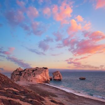 Рок афродита возле петра ту ромиу на кипре, пафос. панорамное изображение знаменитой достопримечательности кипра на романтическом закате
