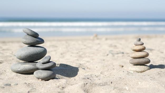 Балансировка скал на берегу океана. камни укладываются в пирамиду из гальки волн морской воды на песчаном берегу.