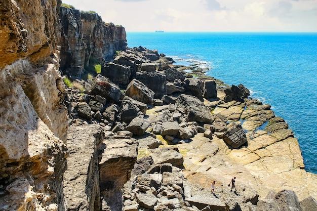 海の横にある岩の崖と人々は水を浴びるために降りてきます。