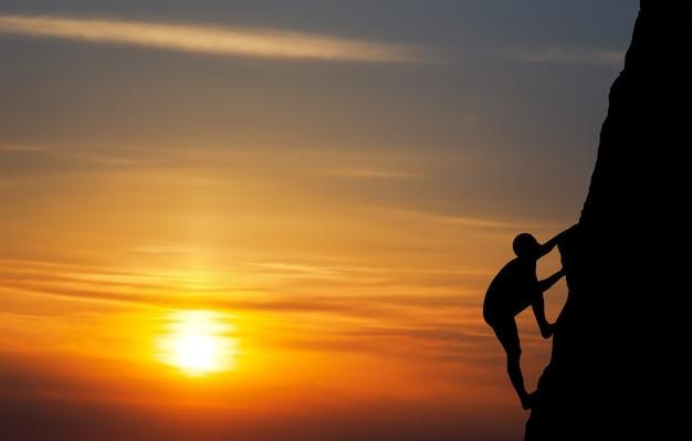 Скалолаз на фоне заката. спорт и активная жизнь