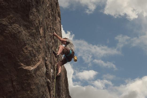 Rock climber climbs a vertical rock