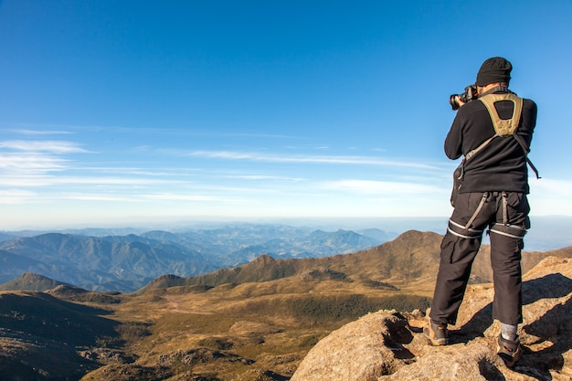 Rock climber photographer shooting landscape on mountain summit