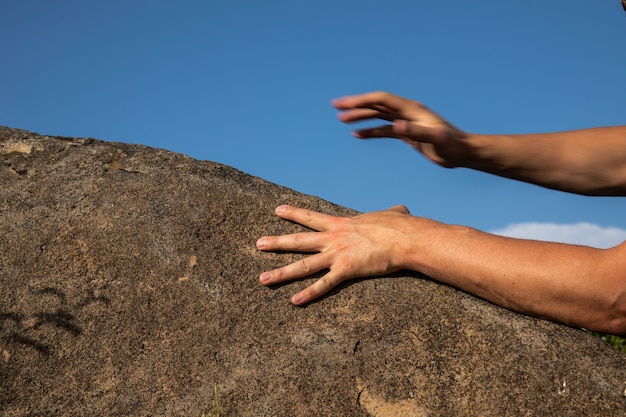 Руки скалолаза на рукоятке на фоне голубого неба.