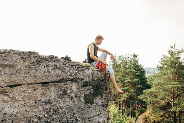Rock climber sitting at the edge of the cliff with a rope