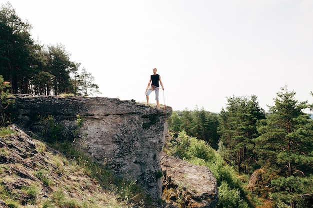 Rock climber standing at the edge of the cliff with a rope