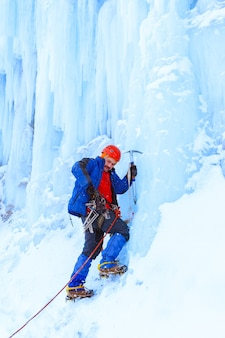 Rock climber with ice ax is preparing to climb a snowy ice wall