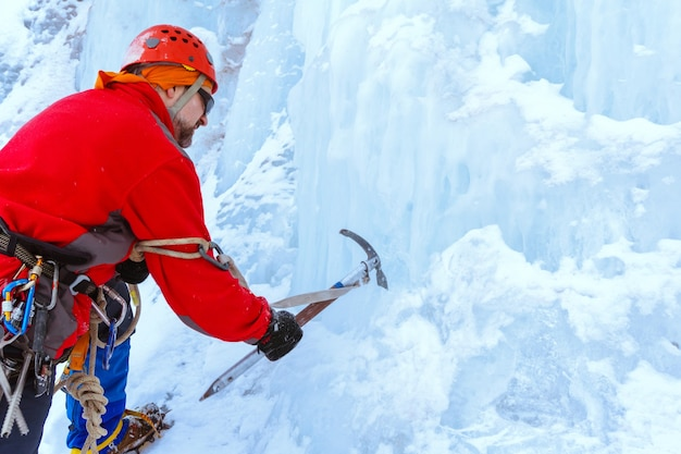 Rock climber with ice axe cuts ice, makes steps in glacier