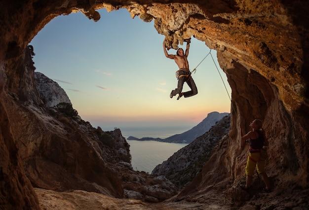 日没時のロッククライミング。若い男が洞窟のルートを登り、女性のパートナーが彼をビレイします。洞窟の形