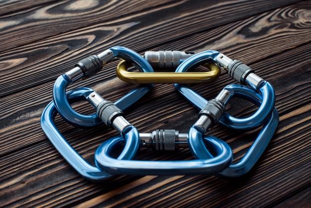 Спортивное скалолазание. изолированное альпинистское снаряжение. части карабинов лежат на деревянном столе.