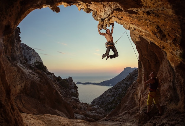 Rock climbing at sunset. young man climbing route in cave, female partner belaying him. cave shaped
