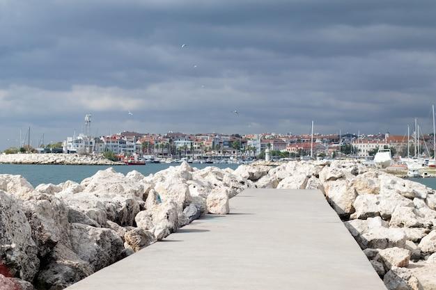 Каменная набережная в море и пристани для судов. грозовое небо и чайки.
