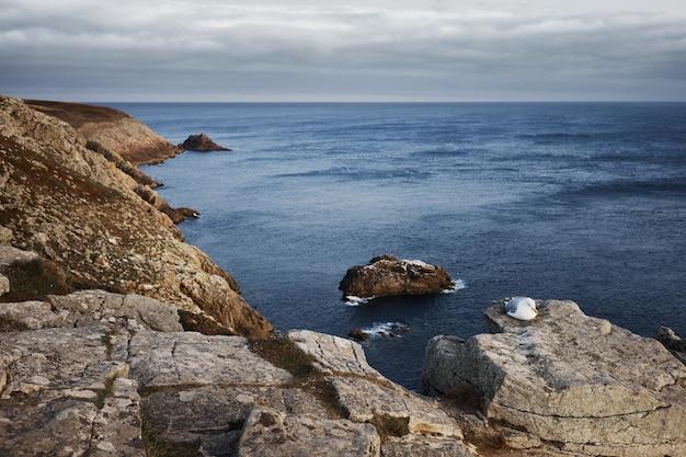 ニンバス雲の下の沿岸岩の近くの岩層島