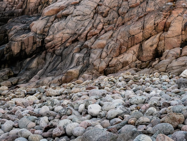 Скальные образования и галька. волновая текстура, горная порода в баренцевом море.