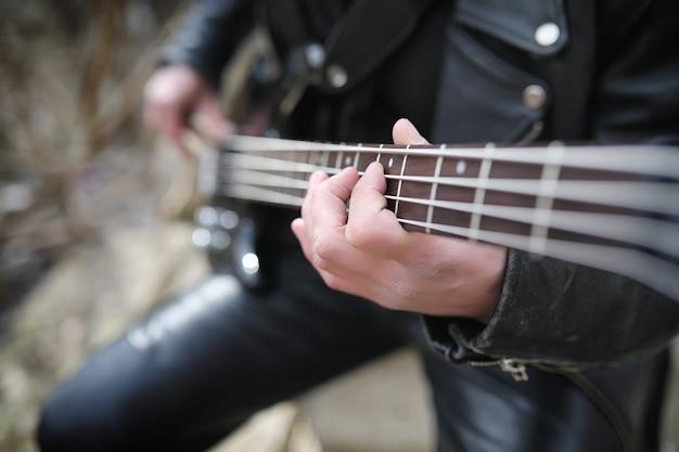 단계에 록 기타리스트입니다. 가죽 슈트에 베이스 기타를 든 음악가. 산업 단계의 배경에 기타와 메탈리스트.