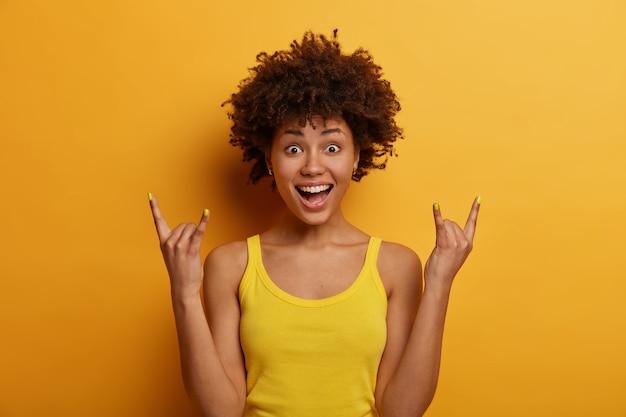 Forza ragazzi! sfacciata donna ribelle dalla pelle scura ha trascorso tutta la notte a una festa rock, mostra gesti heavy metal, si diverte ad ascoltare musica fantastica, sorride ampiamente, vestita in modo casual, isolato su muro giallo