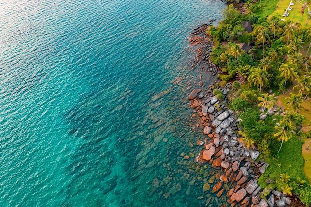 ドローンの角度からはっきりとした海の水まで、海のビーチでロックします。海の後ろの砂が見えます。