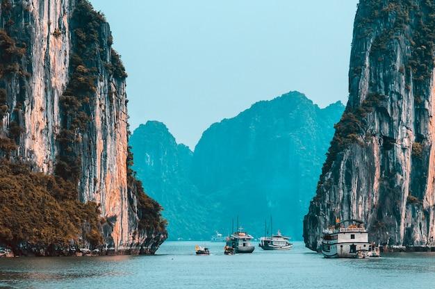 Скальные острова возле плавучей деревни в бухте халонг. красивый морской пейзаж в заливе халонг, вьетнам