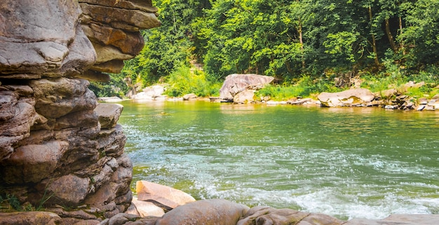 Rock made of many layers of stones near a mountain river in summer