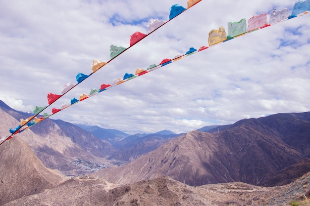 Rock mountain cloudy day prayer flag landscape in shangri la, yunnan province, china