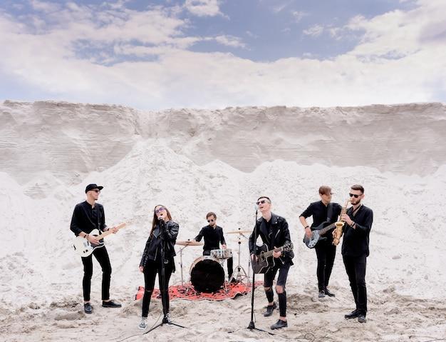해변에서 콘서트를 하는 록 음악 밴드