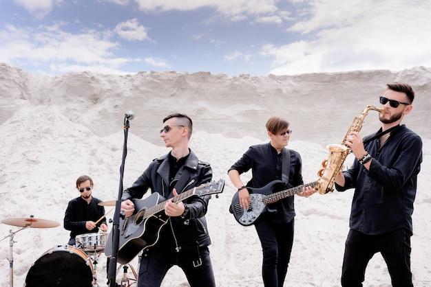 Banda musicale rock che si esibisce in un concerto sulla spiaggia. uomini vestiti con abiti neri in stile rock e occhiali da sole neri