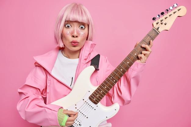 ロックミュージックのコンセプト。驚いた有名なギタリストがベースエレキギターで演奏し、観客の前でスタンジで演奏にショックを受けた人気のロッカーがファッショナブルな服を着ています