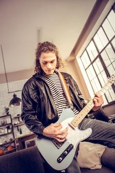 ロックミュージックプレーヤー。新曲を構成する革のジャケットを着た巻き毛の黒髪のロックミュージックプレーヤー