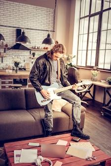 ロックミュージック。ギターを弾く革のブーツを身に着けている才能のあるスタイリッシュなロック音楽愛好家