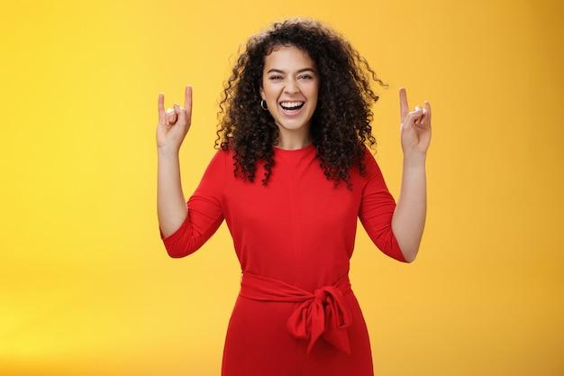 ロックンロールライブ。カリスマ的な興奮した赤いドレスを着た若い縮れ毛の女性は、お気に入りのバンドのコンサートを待っている間、手を上げてロックジェスチャーを見せ、スリルと幸せに笑っています。
