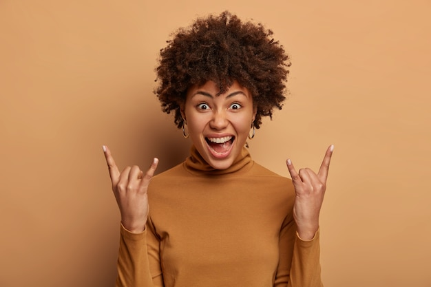 ロックンロールは永遠に生きる感情的な暗い肌の女性はヘビーメタルのサインを作ります