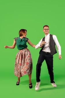 Rock n roll. dancing alla moda della giovane donna della vecchia scuola isolato sul fondo verde dello studio. giovane uomo e donna alla moda.