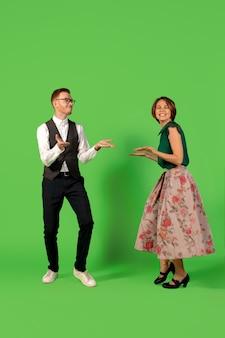 ロックンロール。緑のスタジオの背景に分離して踊る昔ながらのファッションの若い女性。若いスタイリッシュな男性と女性。
