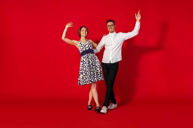 락앤롤. 구식 구식 된 젊은 여자 춤에 고립 된 빨간색 스튜디오 배경. 세련 된 젊은 남자와 여자.