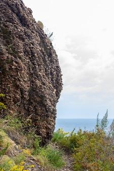 Скала из мелких гальковидных камней над озером байкал. рядом проходит пешеходная тропа с травой. вертикальное изображение.