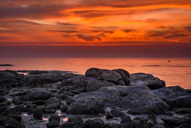 夕焼けの空を持つ海の岩