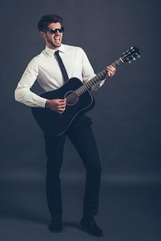 Рок или бизнес-звезда? в полный рост красивый хорошо одетый молодой человек в солнечных очках играет на гитаре и держит рот открытым, стоя на сером фоне