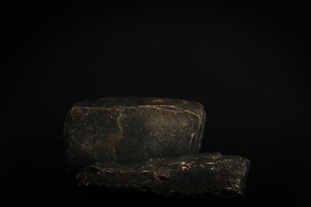 黒の背景に表彰台をロックします。製品、化粧品のプレゼンテーションのための石のポデスト。クリエイティブなモックアップ。美容製品の台座またはプラットフォーム。