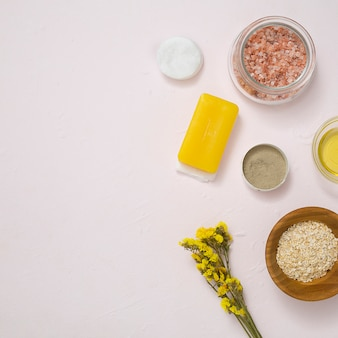 Rock salt; cotton pads; soap; oats; yellow limonium flower and cosmetics products on white concrete surface