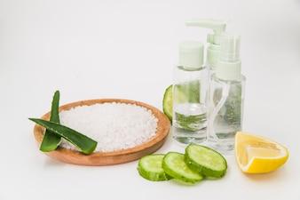Rock salt on wooden plate; cucumber slices; lemon and spray bottle on white backdrop