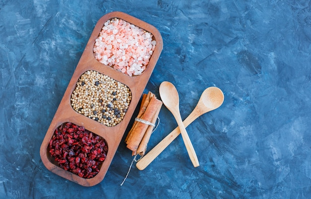 Rock salt in wooden plate with dried barberries, quinoa, black pepper, cinnamon sticks, spoons flat lay on blue grunge background