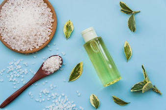 Rock salts; leaves and spray bottles on blue background