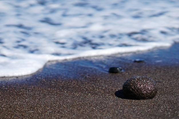 Rock on the sand on the paradisos beach of santorini