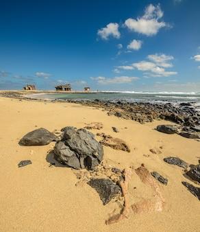 Каменистый песчаный пляж кабо-верде с домиками вдалеке