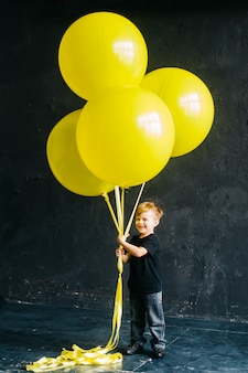 Мальчик рок-звезды с большими желтыми воздушными шарами. стильный малыш на черном фоне.