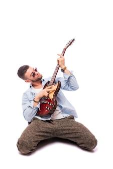 白い壁に分離されたギターを持つロックスターの男