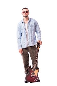 Uomo della rock star con una chitarra isolata sopra la parete bianca
