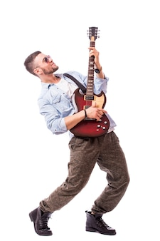 Rock star man with a guitar isolated over white wall