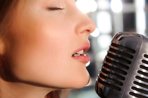 ロックスター。レトロなマイクで歌うセクシーな女の子。