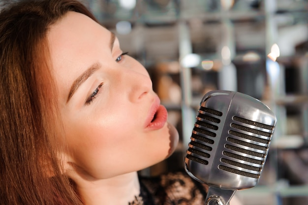 Rock star. sexy girl singing in retro microphone.